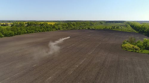 Aerial View of Agricultural Tractor Cultivating Field.
