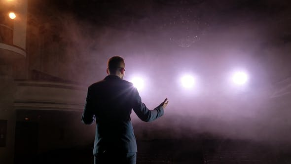 Thumbnail for Showman. Young Male Entertainer, Presenter or Actor on Stage. Back, Arms To Sides, Smoke on