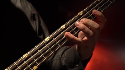 Bass Guitar. Fingers Fingering the Strings.