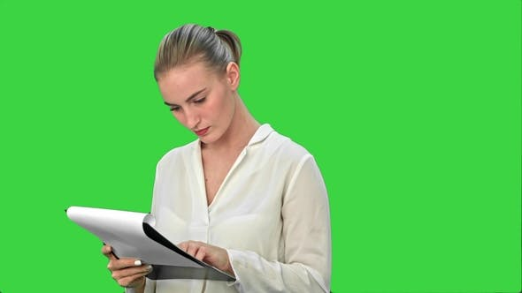 Thumbnail for Young Businesswoman Reading Documents on a Green Screen, Chroma Key.