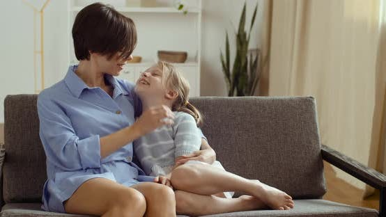 Thumbnail for Cute Adorable Funny Little Kid Daughter Hugs and Kisses Young Mum, Family Playing on Sofa at Home