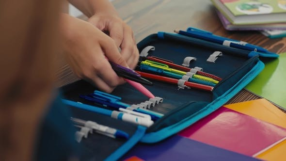 Student Puts Pens and Pencils in the Pencil Case