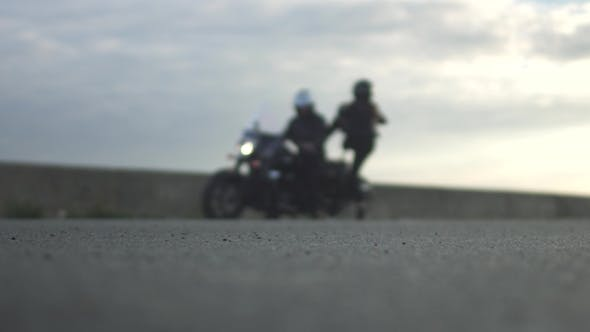 Thumbnail for Young Couple on Motorcycle Is Quarreling at Blurred Background
