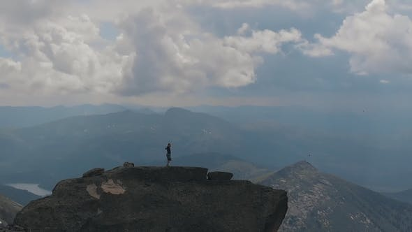 Cover Image for Aerial Shot of Silhouette of a Male Climber Standing on Top of a Mountain Happily Raising His Hands.