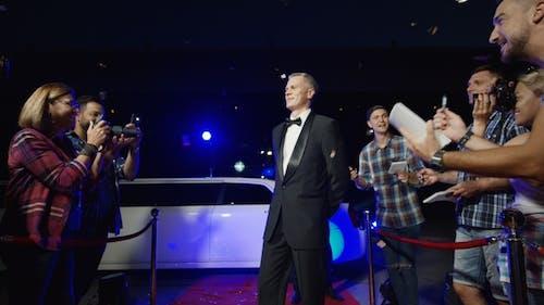 Adult Celebrity Giving Autographs on Red Carpet