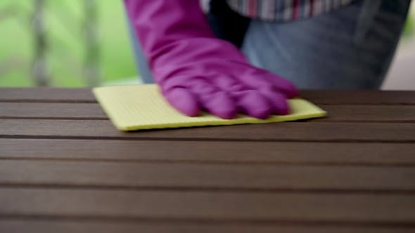 Thumbnail for Hand in the Violet Glove Cleans Wooden Table on the Terrace Using Yellow Rag
