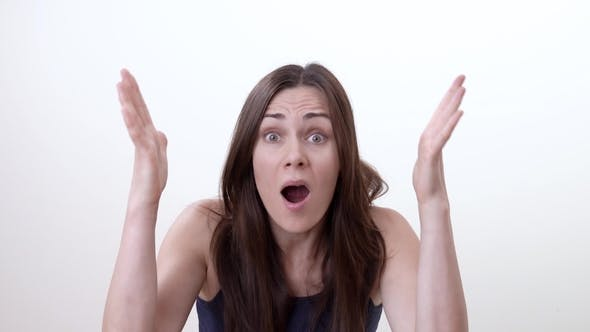 Thumbnail for Portrait of Very Surprised Brunette Woman. She Raises Her Hands and Grabs Her Head. Isolated on the