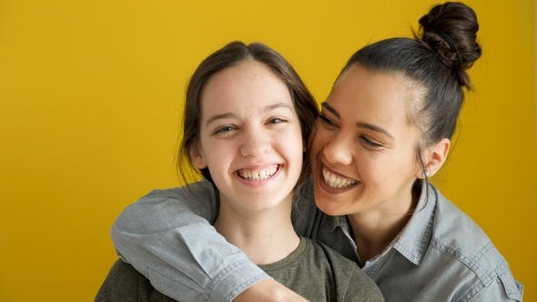 Thumbnail for Happy Laughing Sisters on Yellow Background
