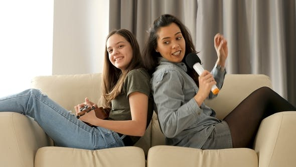 Thumbnail for Happy and Positive Sisters Playing and Singing on the Sofa