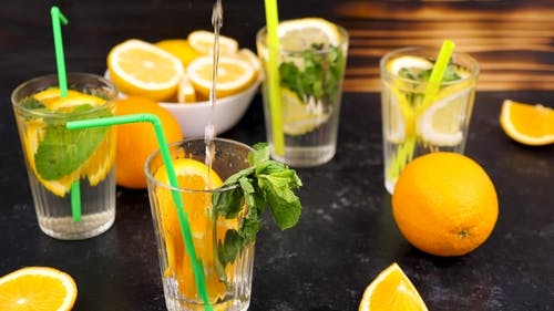 Pouring Water in a Glass with Slices of Oranges Next To Glasses with Lemonade