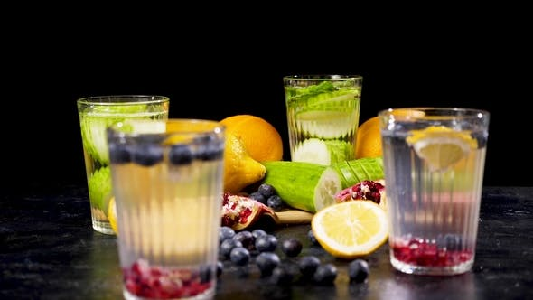 Thumbnail for Different Fruits and Berries on a Wooden Board Next To Four Glasses of Detox Water