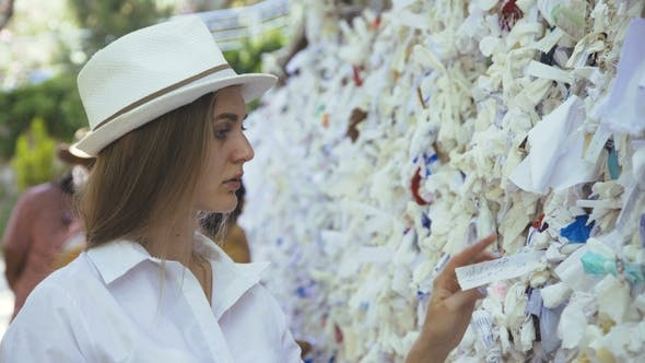 The Female Pilgrim Thoughtfully Touches Wish Clothes Attached on Wish Wall