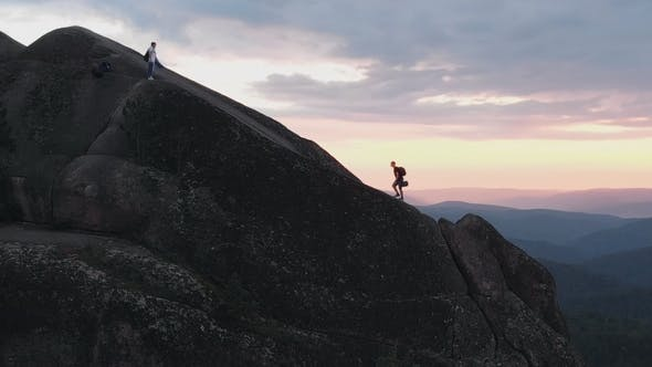 Thumbnail for Aerial Shot of Two Friends of Tourists Climb a High Rock at Sunset.