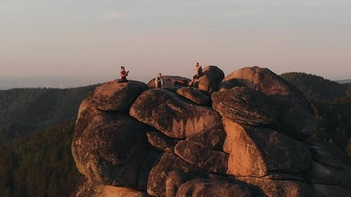 Epic Drone Shot of Friends Enjoy the Sunset Sitting on Top of a High Mountain in the Siberian Stolby