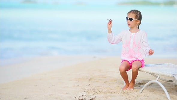 Thumbnail for Happy Little Girl with Toy Airplane in Hands on White Beach