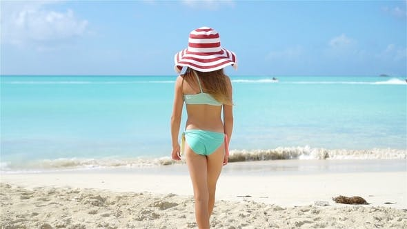 Thumbnail for Adorable Little Girl in Big Hat Walking entlang White Sand Beach
