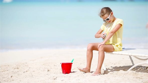 Cover Image for Little Girl with Bottle of Sun Cream Sitting at Tropical Beach