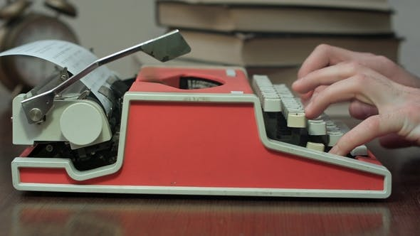 Thumbnail for Man's Hands Typing on a Red Mechanical Typewriter