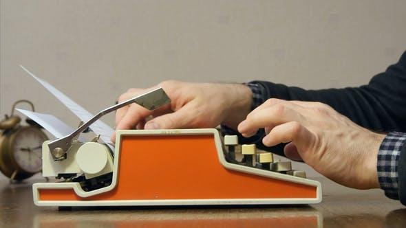 Thumbnail for Männliche Hände Tippen auf die alte rote Schreibmaschine am Schreibtisch mit Bücher