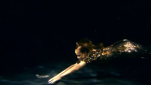 Little Mermaid Girl Is Floating Under Water and Taking From a Bottom a Brilliant Crown