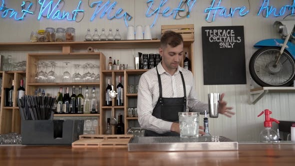 Thumbnail for Flair Bartending. A Handsome Young Bartender Pours a Blue Curacao Liquor Into a Glass with Ice Cubes