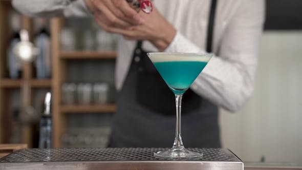 Thumbnail for of Handsome Young Bartender Hands Adding a Whipped Cream To Blue Colored Cocktail. Finishing Making