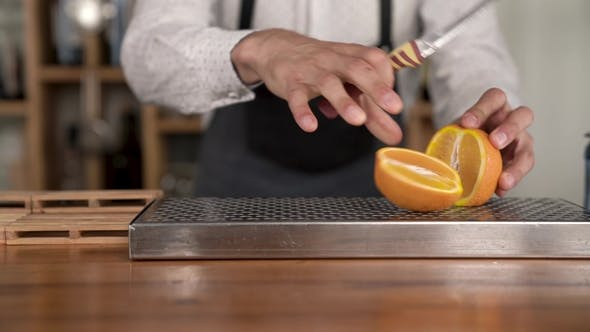 Thumbnail for Bartender Hands Cuts the Orange Fruit on the Bar Counter, Before Making a in the Cocktail