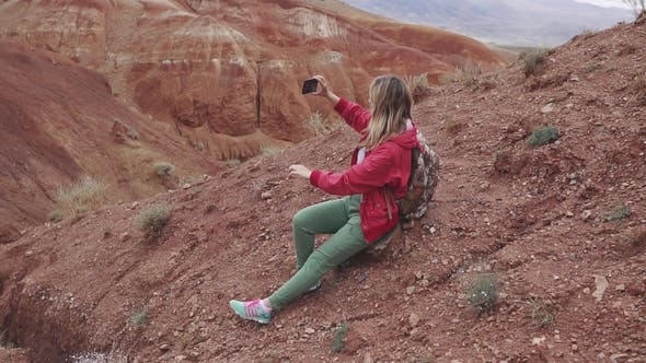 Thumbnail for Girl Tourist Makes Photos on the Camera Smartphone Red Mountains and Red Earth As on Mars