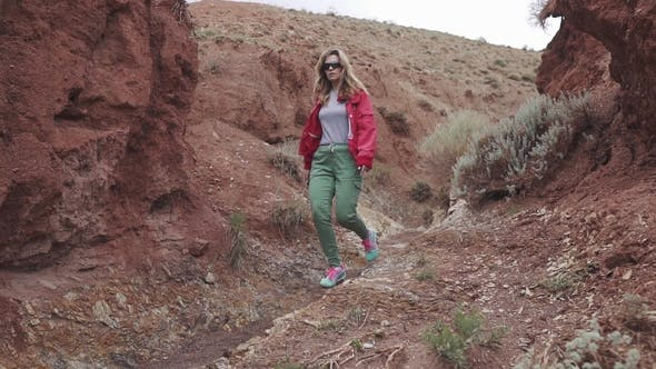Thumbnail for Girl Tourist in Sunglasses Goes on an Unusual Terrain Red Mountains and Red Earth As on Mars