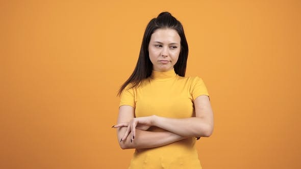 Unhappy Woman on Vivid Orange Background