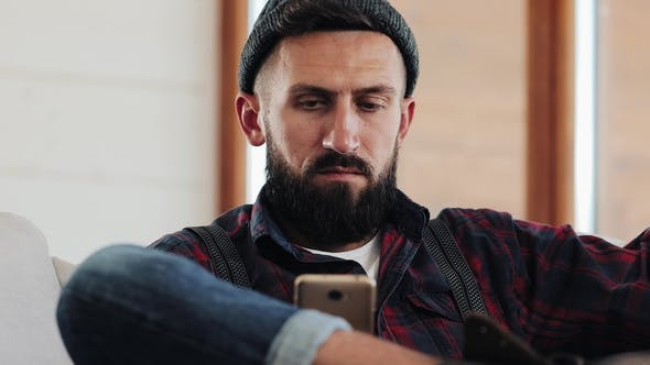 Thumbnail for Attractive Bearded Man with Smartphone Sitting on Sofa at Modern Loft Home in the Living Room and