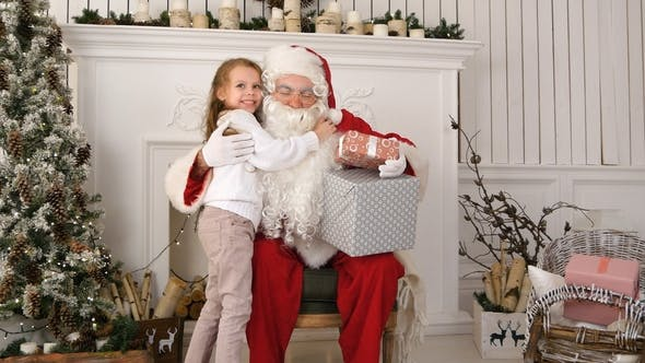 Thumbnail for Santa Claus Holding Presents and Hugging a Little Cute Girl