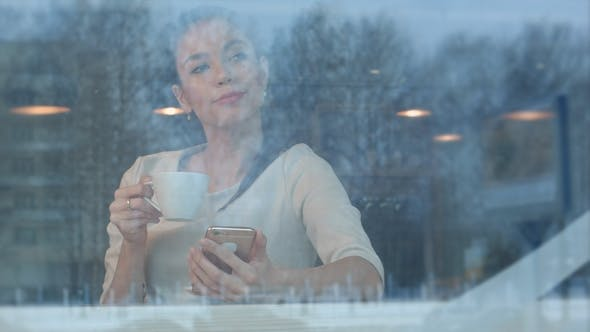 Thumbnail for Beautiful Girl Using Phone While Drinking Coffee in a Cafe Viewed Through Window
