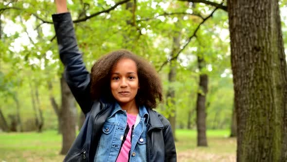 Thumbnail for Young African Surprised Girl Jumps and Raises Arms Up To the Sky in the Park - Satisfied