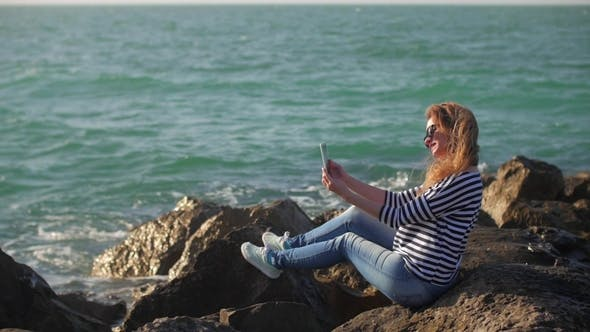 Cover Image for Blonde Girl with Tablet in Hands Is Sitting on a Huge Stones Shore in Sunny Summer Day