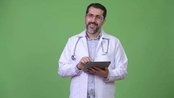 Thumbnail for Handsome Persian Bearded Man Doctor Thinking While Using Digital Tablet
