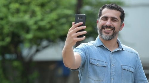 Handsome Persian Bearded Man Taking Selfie in the Streets Outdoors