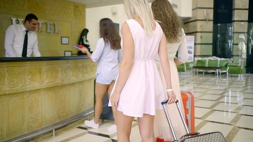 Three Beautiful Women with Suitcases Are Approaching To Front Desk in Luxury Hotel, Receptionist Man