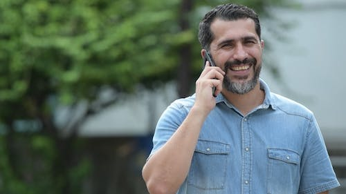 Persian Bearded Man Talking on Phone in the Streets Outdoors