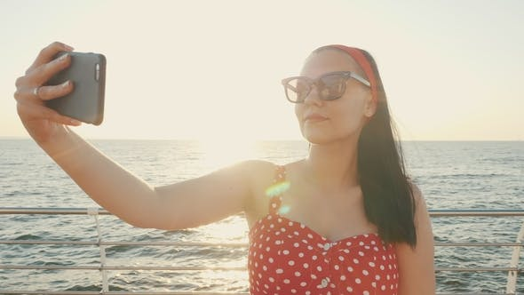 Thumbnail for Pretty Woman Using Black Mobile Phone By the Sea Beach. Girl in Retro Red Polka Dots