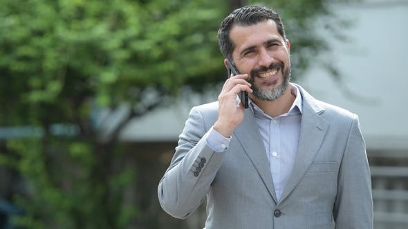 Persian Bearded Businessman Talking on Phone in the Streets Outdoors