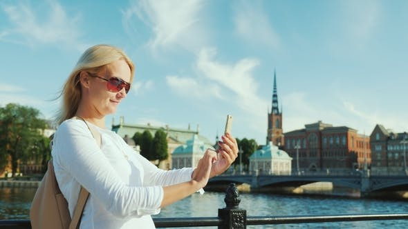 Thumbnail for A Young Woman Photographes Herself with a Smartphone Against the Backdrop of Stockholm's City Line
