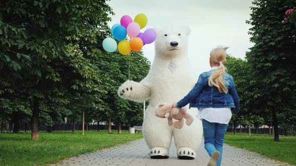 Cover Image for Happy Childhood. A Little Girl with Fair Hair Runs To Meet a Big White Bear, She Has a Teddy Bear in