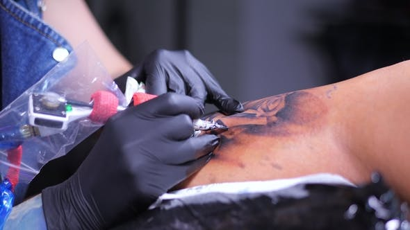 Thumbnail for Tattoo Artist Demonstrates Process of Getting Black Tattoo with Paint and Machine. Woman Works in