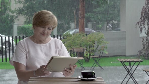 Thumbnail for An Attractive Aged Woman with a Cup of Tea Reading and Typing on a Tablet in the Terrace, Smiling
