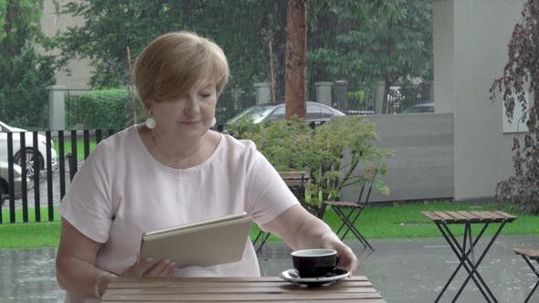 Thumbnail for Aged Woman at the Terrace Is Reading a Tablet and Enjoying a Cup of Tea. Heavy Rain Is Falling in