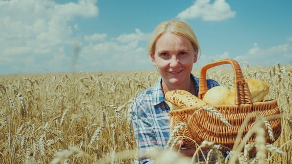 Cover Image for Woman Farmer with a Basket with Bread and Rolls on a Mature Wheat Field. Good Harvest, Organic