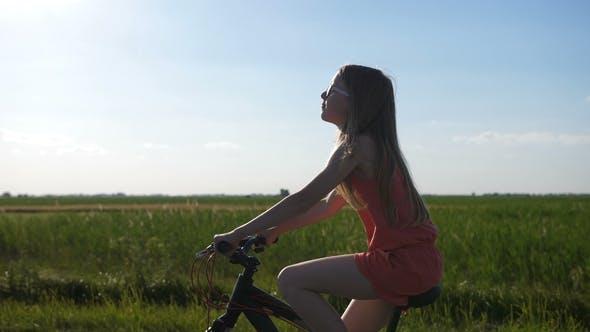 Cute Teen Girl Riding Bike in Countryside
