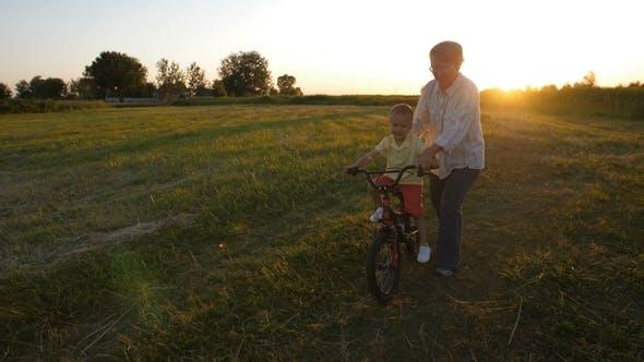 Thumbnail for Grandmother Teaching Grandson To Ride a Bike