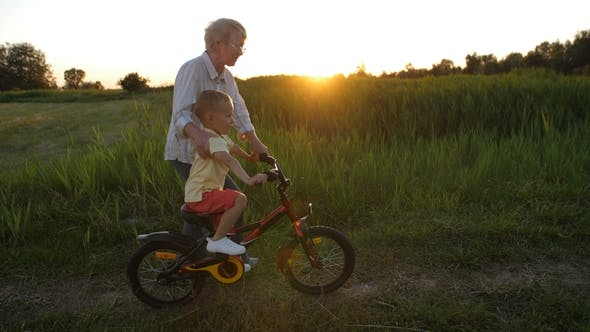 Thumbnail for Toddler Boy Riding Bicycle with Grandmother's Help